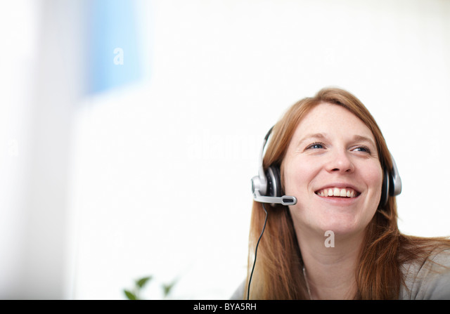 Happy girl with headset next to computer - Stock Image