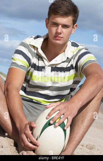 Teenage Boy Sitting On Beach Holding Rugby Ball - Stock Image