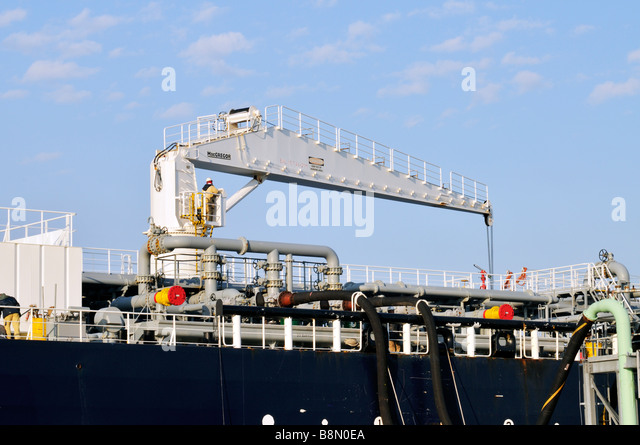 Workers operating a [hydraulic hose handling crane] on the deck of an 'oil tanker' with pipes & hoses - Stock Image