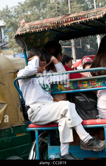 Tired schoolboy going home on a rickshaw, Old Delhi, India - Stock Image