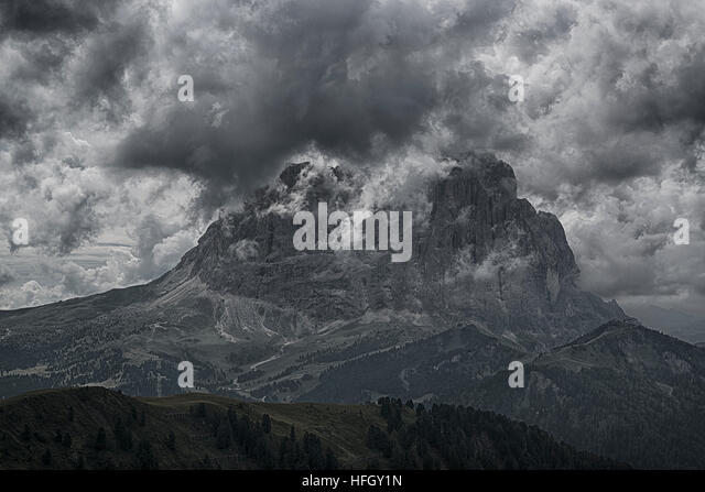 The Top of Langkofel in the clouds seen from Dantercepies, summer afternoon - Val Gardena, Dolomites - Stock Image
