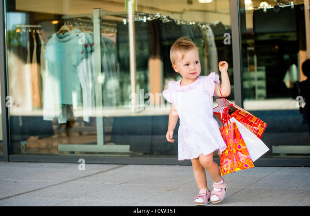 Cute baby goes shopping with bags, shops in background - Stock Image