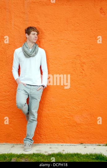 Cool young man standing by the orange wall - Stock-Bilder