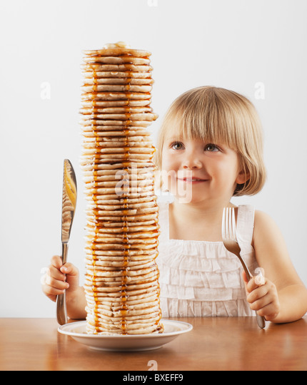 Young girl sitting behind a tall stack of pancakes - Stock-Bilder