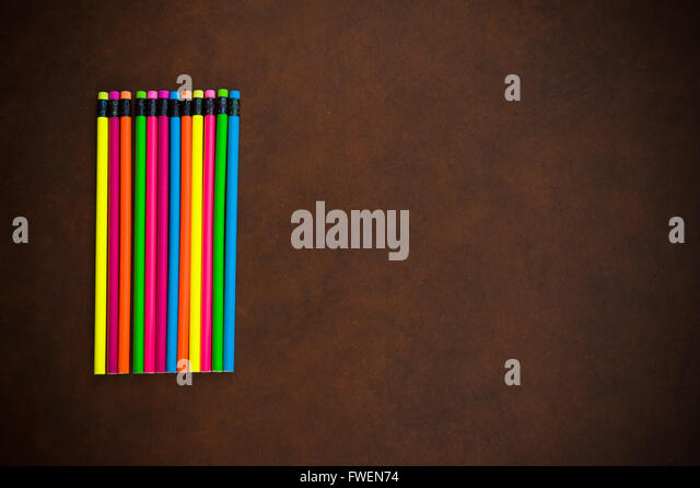 Wooden desktop with colorful pencil on the left side, red yellow, blue, green and purple - Stock Image