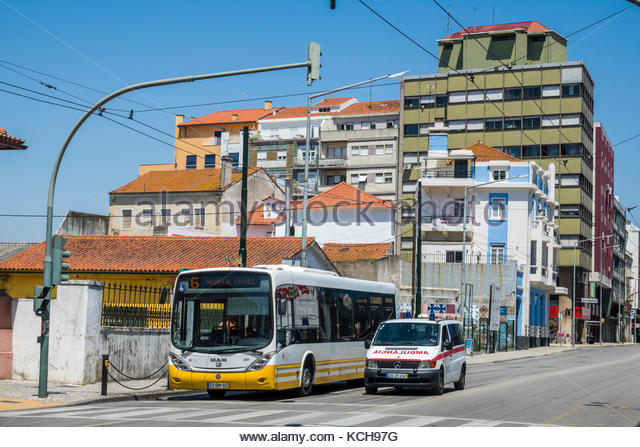 Coimbra Portugal historic center Avenida Fernao de Magalhaes intersection traffic light bus ambulance stopped buildings - Stock Image