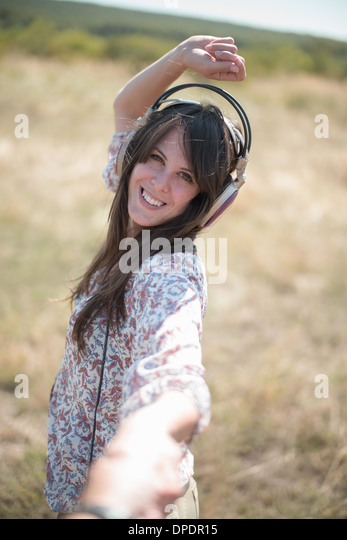 Portrait of mid adult woman dancing in field with arms raised, wearing headphones - Stock Image