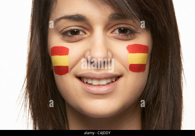 Young Female Sports Fan With Spanish Flag Painted On Face - Stock Image