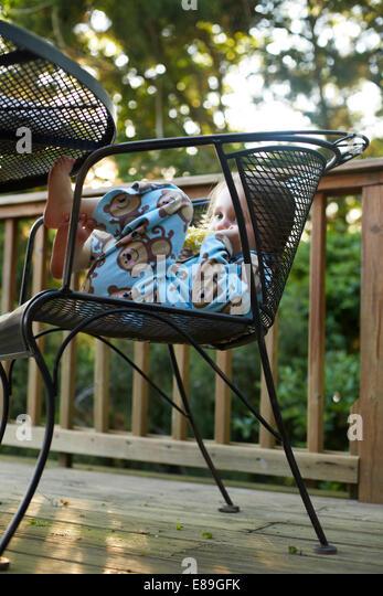 Child resting on chair on deck - Stock-Bilder