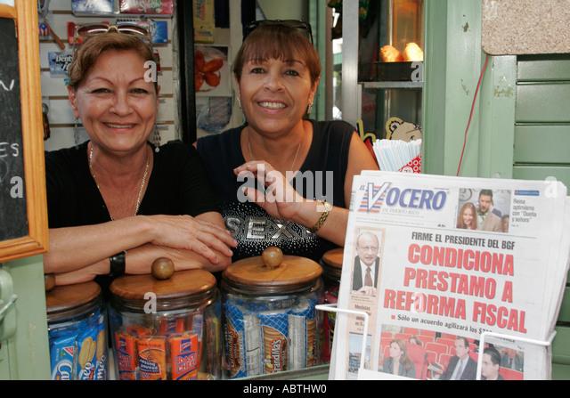 Puerto Rico Old San Juan Plaza de Armas Hispanic women food vendor Spanish language newspaper - Stock Image