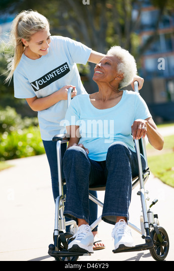 Teenage Volunteer Pushing Senior Woman In Wheelchair - Stock Image