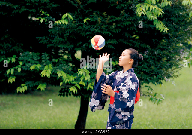 Girl in kimono playing with paper balloon - Stock-Bilder