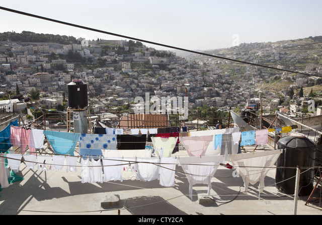 Clotheslines of laundry drying and black solar hot water heaters on a rooftop in East Jerusalem, Israel - Stock Image