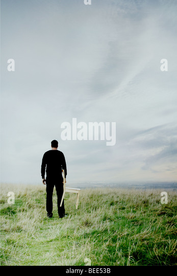man standing on hill with a chair - Stock-Bilder