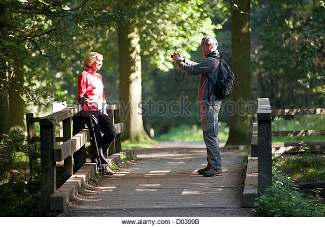 A mature man taking a photograph of his partner in the countryside - Stock Image