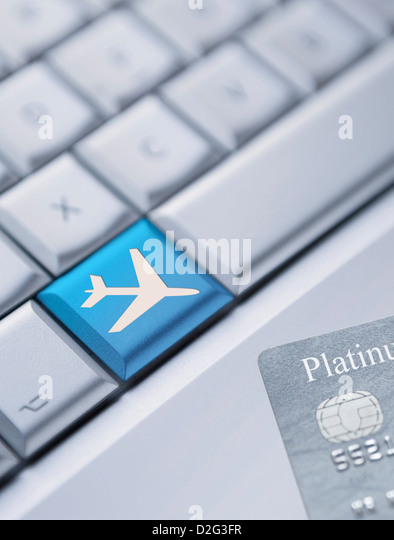 Detail of a laptop keyboard with one blue key with an plane symbol on it and a credit card at the bottom right corner - Stock-Bilder