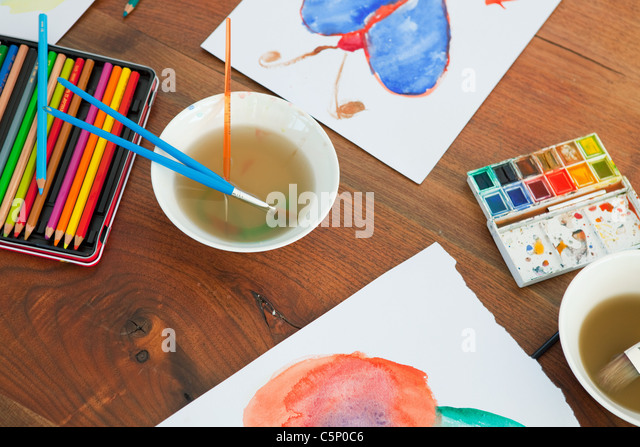 Children's paintbrushes and paintings on table - Stock-Bilder
