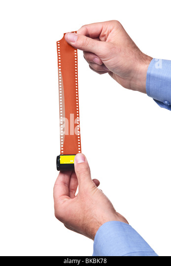 Hands holding a roll of blank colour 35mm film, isolated on a white background. Add your own negative frames. - Stock Image