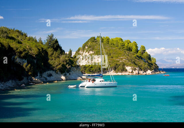 Lakka, Paxos, Ionian Islands, Greece. View across the clear turquoise waters of Lakka Bay, yacht at anchor. - Stock Image