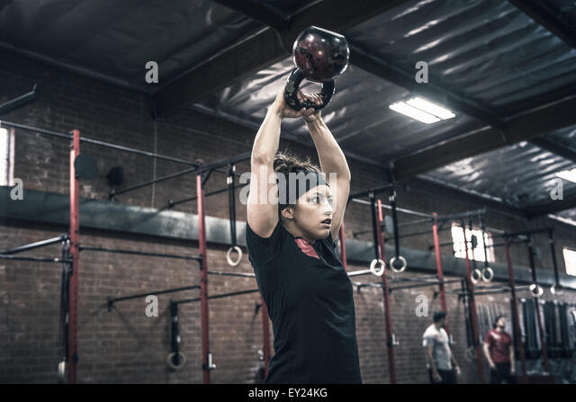 Young woman holding up kettle bells in gym - Stock-Bilder