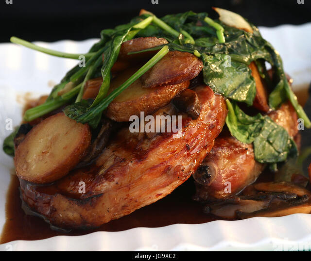 Wilted spinach over pork chops with mushroom gravy and roasted potatoes on white ridged dish - Stock Image
