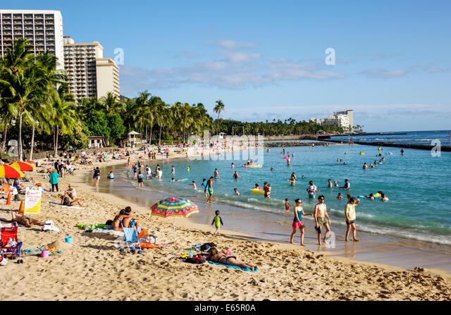 Hawaii Hawaiian Honolulu Waikiki Beach resort Kuhio Beach State Park Pacific Ocean sunbathers families - Stock Image