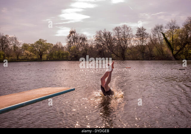 A young man swimming in spring fresh water ponds. - Stock Image