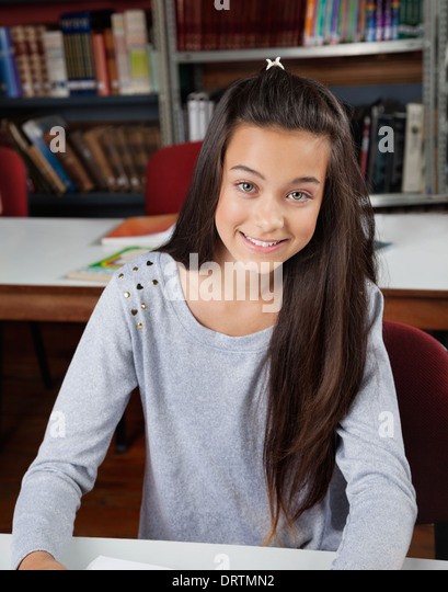 Happy Female Student Sitting In Library - Stock Image