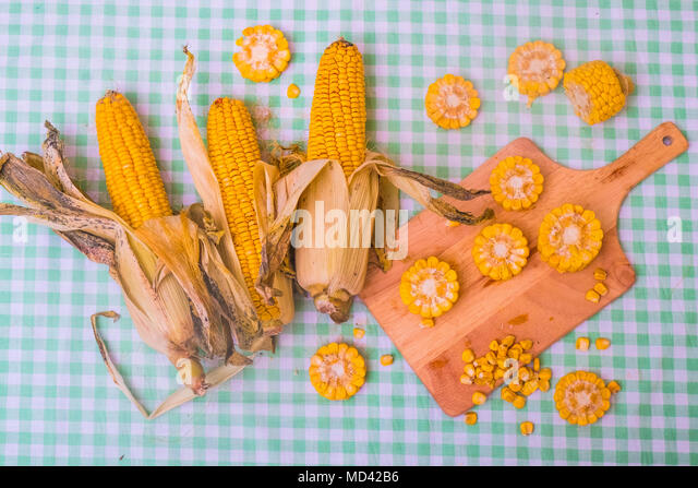 Sliced corn on the cob on chopping board, with whole corn on cob, overhead view - Stock Image