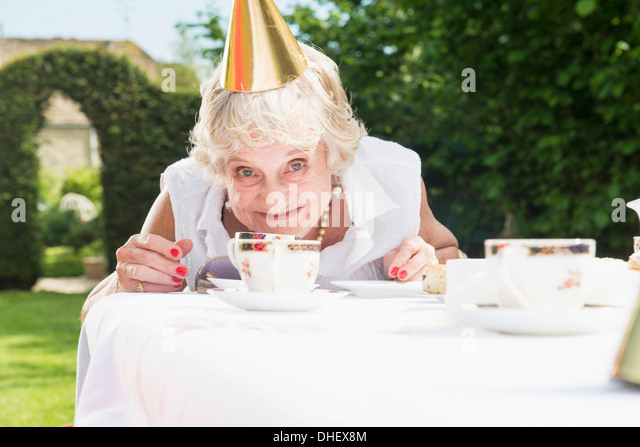 Senior woman wearing party hat looking at camera, smiling - Stock Image