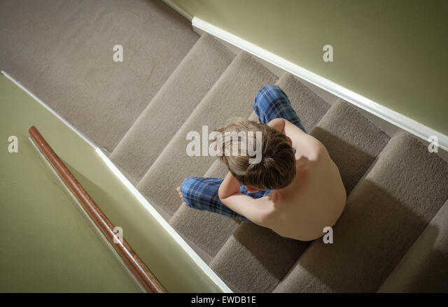 A child sitting on the stairs with his head in his hands looking upset - Stock-Bilder