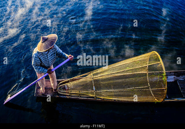 High angle view of Asian fisherman using fishing net in canoe on river - Stock Image