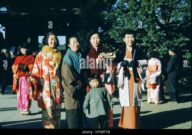 A Japanese family, with the women wearing traditional colorful robes and kimonos, poses for a picture in front of - Stock Image