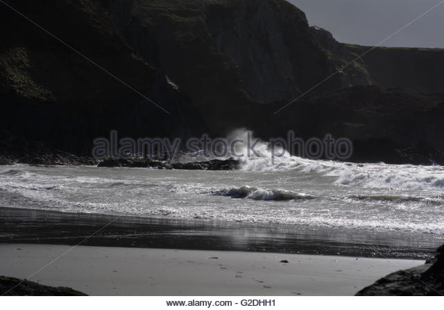 Storm at sea smashing over shore rocks - Stock Image