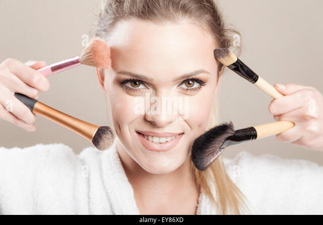 Young woman holding makeup brushes - Stock Image
