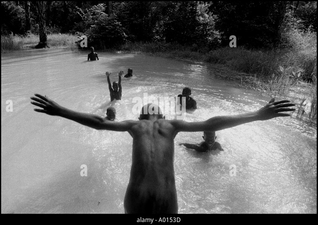 Briama Balde dives into the toufee with his friends in a small Muslim village in Guinea Bissau Photo by Ami Vitale - Stock Image