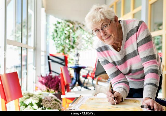 Elderly woman painting - Stock-Bilder