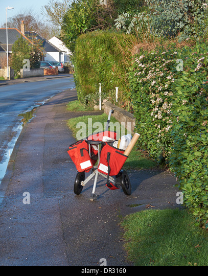 Postman's mail trolley parked while delivering to a house - Stock Image