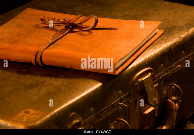 old, vintage, antique leather suitcase with leather bound and tied book on top painted with warm light - Stock Image