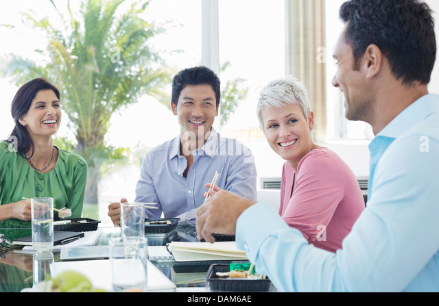 Business people smiling in lunch meeting - Stock Image