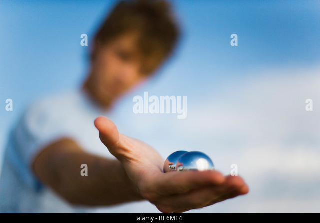 Man holding yin yang balls in hand, close-up - Stock Image