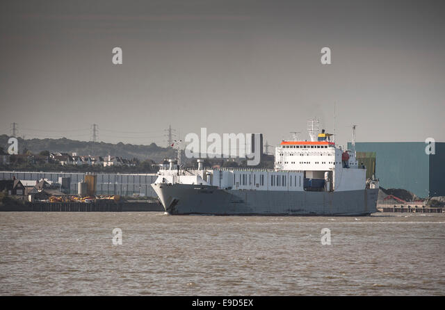 The Ro-ro cargo carrier steaming downriver on the River Thames. - Stock Image