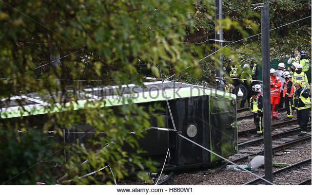 Members of the emergency services work next to a tram after it overturned injuring and trapping some passengers - Stock-Bilder