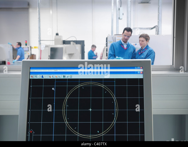 Engineers and CAD drawing on monitor - Stock Image