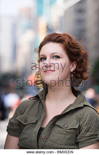 Portrait of young woman in street - Stock Image