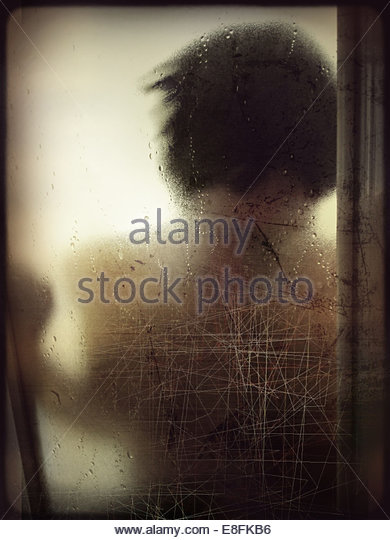 Woman leaning on window - Stock Image