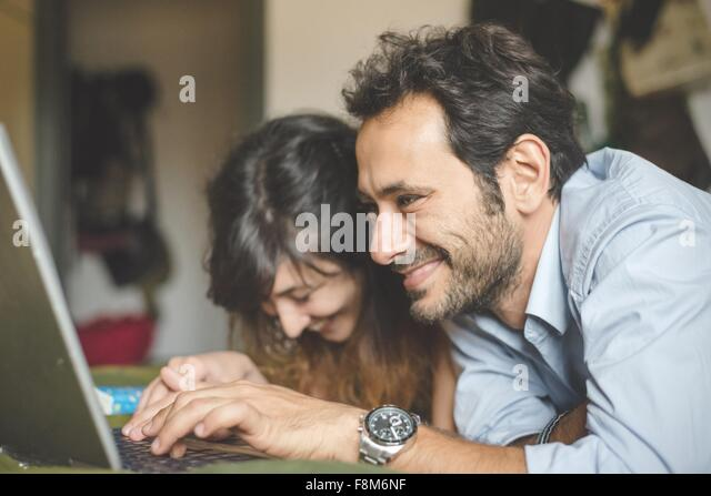 Head and shoulders of young couple lying on front using laptop computer - Stock-Bilder