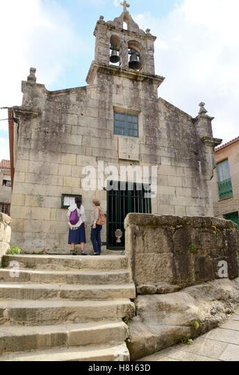 Twon women in front a church in Combarro  a viallge of the province of Pontevedra, in Galicia, Spain. - Stock Image
