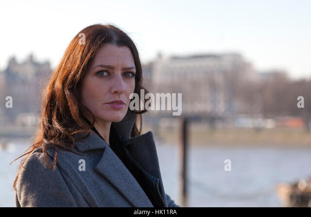 An attractive woman with long dark hair looks towards the camera with a river in the background - Stock Image