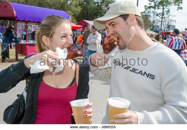 Deerfield Beach Florida Quiet Waters Park Florida Renaissance Festival man woman couple eat turkey leg food - Stock Image